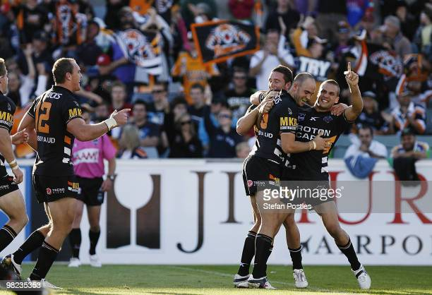 Tigers players celebrate after Liam Fulton scored a try during the round four NRL match between the Canberra Raiders and the West Tigers at Canberra...