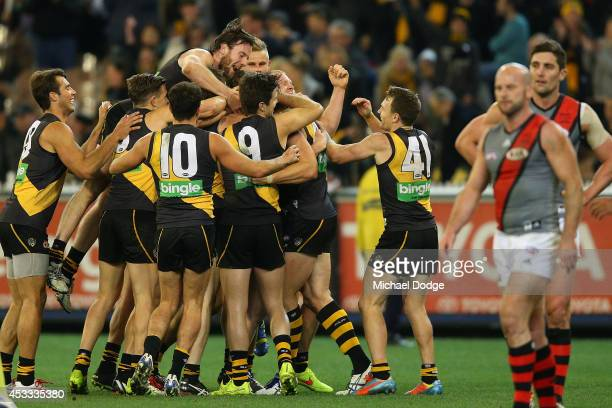 Tigers players celebrate their win during the round 20 AFL match between the Richmond Tigers and the Essendon Bombers at Melbourne Cricket Ground on...