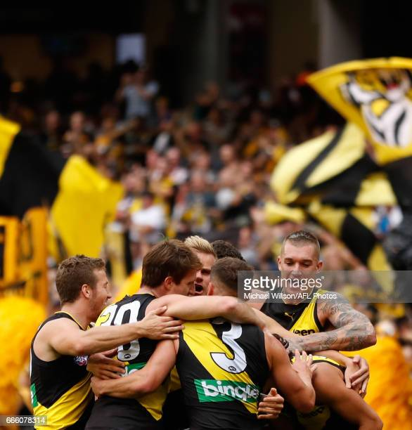 Tigers players celebrate with Daniel Rioli of the Tigers after he goaled from the boundary during the 2017 AFL round 03 match between the Richmond...