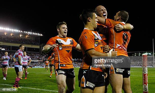 Tigers players Chris Lawrence Luke Brooks Cory Paterson and Robbie Farah celebrate a try during the round 10 NRL match between the CronullaSutherland...