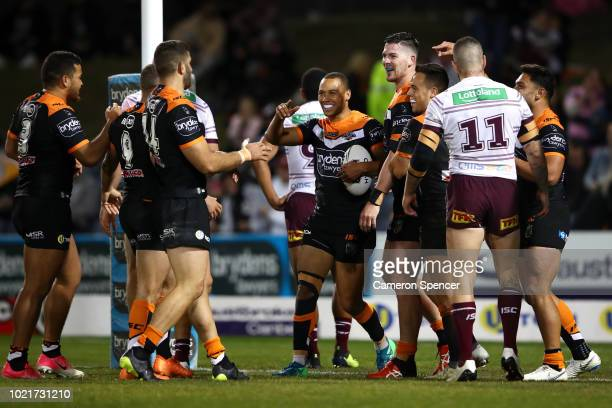 Tigers players congratulate Moses Mbye of the Tigers after scoring a try during the round 24 NRL match between the Wests Tigers and the Manly Sea...