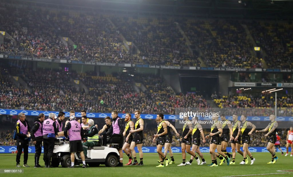 Tigers players console teammate Reece Conca as he is stretchered from the field during the 2018 AFL round15 match between the Richmond Tigers and the Sydney Swans at Etihad Stadium on June 28, 2018 in Melbourne, Australia.