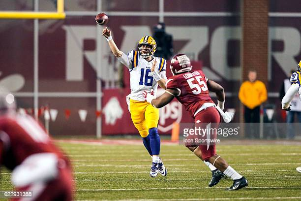 Tigers quarterback Danny Etling passes the ball as Arkansas Razorbacks defensive lineman Jeremiah Ledbetter pursues during an NCAA football game...