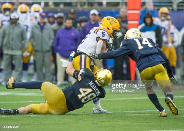 Tigers running back Derrius Guice complete a first down as Notre Dame Fighting Irish linebacker Greer Martini makes the tackle during the Citrus Bowl...