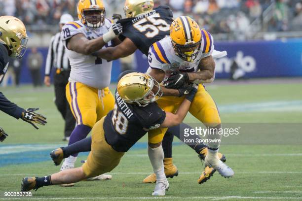 Tigers running back Derrius Guice is tackled by Notre Dame Fighting Irish linebacker Greer Martini during the second half of the Citrus Bowl game...