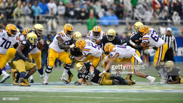 Tigers running back Derrius Guice is tackled by Notre Dame Fighting Irish linebacker Drue Tranquill during the first half of the Citrus Bowl game...