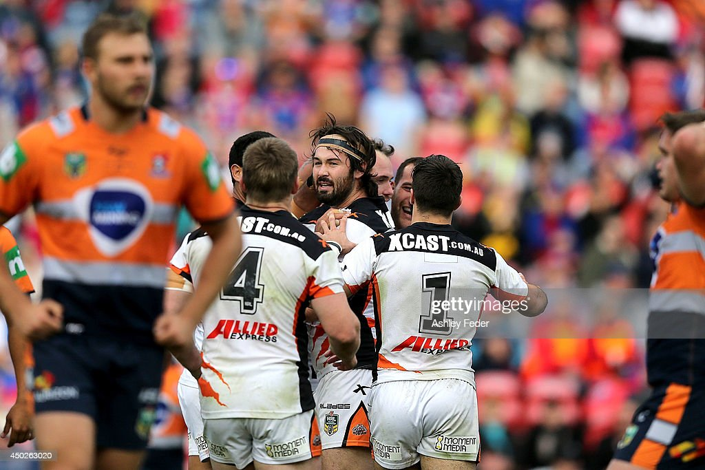 Tigers teammates celebrate a try with Knights players looking dejected in the background during the round 13 NRL match between the Newcastle Knights and the Wests Tigers at Hunter Stadium on June 8, 2014 in Newcastle, Australia.