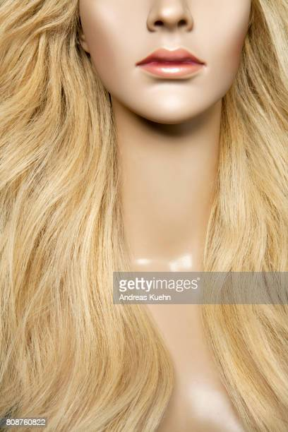 Tight crop of a nuude, young female mannequin with a long, wavy, blond, human hair wig and pale skin.