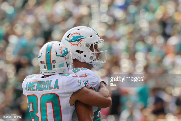 Tight end AJ Derby of the Miami Dolphins celebrates his touchdown with teammate wide receiver Danny Amendola against the New York Jets in the second...