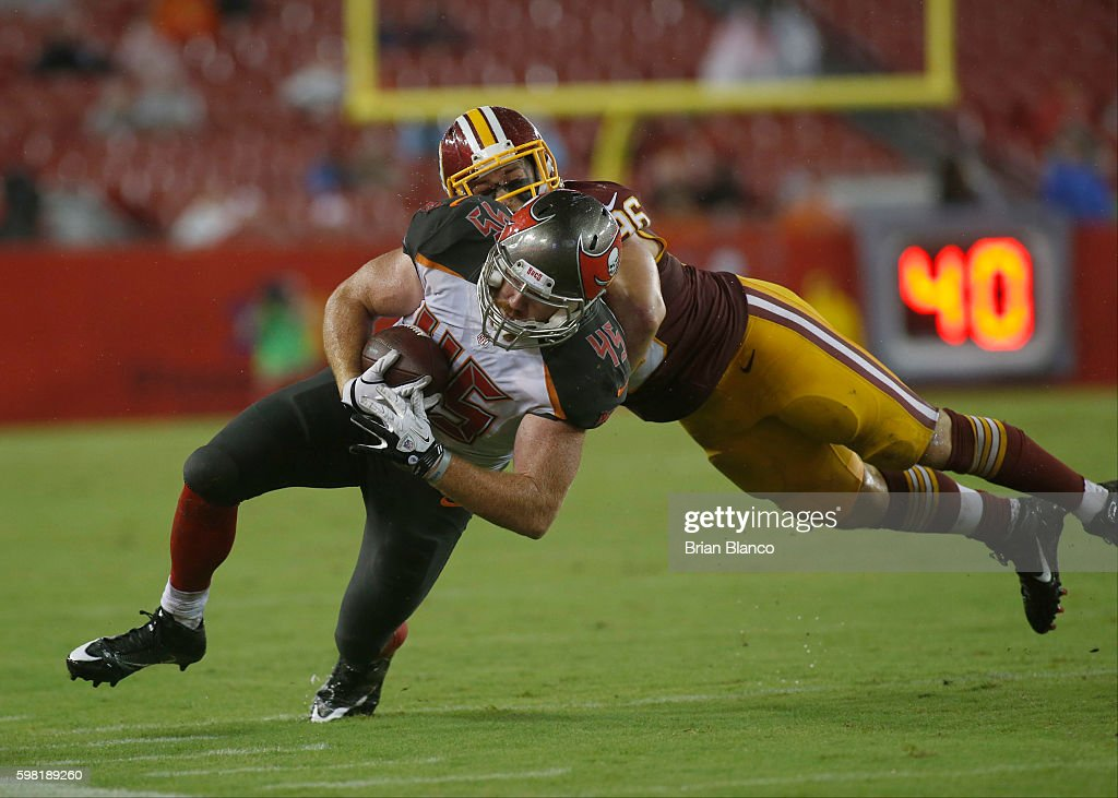 Tight end Alan Cross #45 of the Tampa Bay Buccaneers runs for a first down while getting pressure from linebacker Houston Bates #96 of the Washington Redskins during the fourth quarter of an NFL preseason game on August 31, 2016 at Raymond James Stadium in Tampa, Florida.