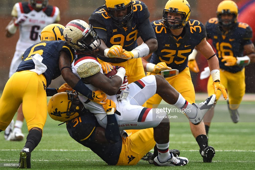 Tight end Andrew Isaacs #44 of the Maryland Terrapins is hit by linebacker Isaiah Bruce #31 of the West Virginia Mountaineers and teammates in the second quarter during an NCAA college football game at Capital One Field at Byrd Stadium on September 13, 2014 in College Park, Maryland.