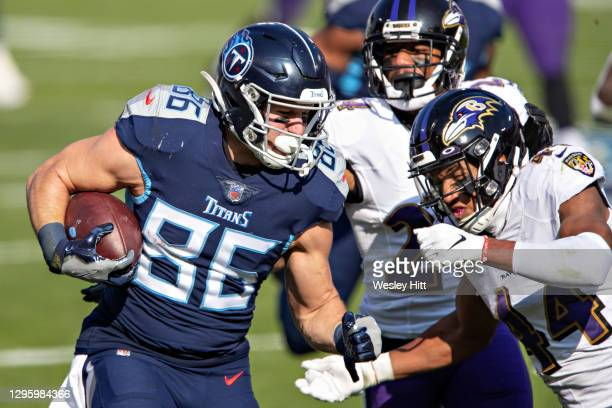 Tight end Anthony Firkser of the Tennessee Titans runs the ball and is tackled during their AFC Wild Card Playoff game by cornerback Marlon Humphrey...