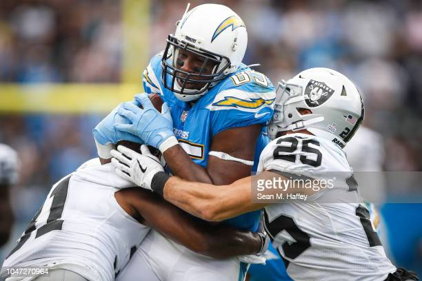 Tight end Antonio Gates of the Los Angeles Chargers is tackled by defensive back Erik Harris of the Oakland Raiders in the third quarter at StubHub...