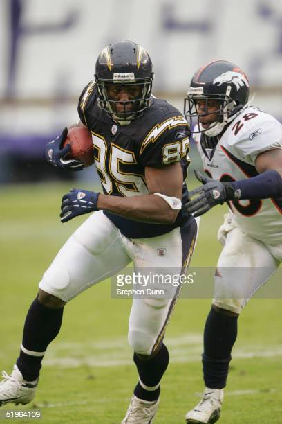 Tight end Antonio Gates of the San Diego Chargers attempts to evade safety Kenoy Kennedy of the Denver Broncos during the game on December 5 2004 at...