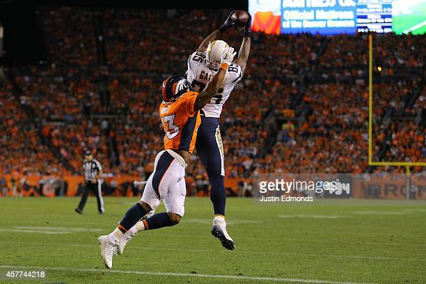 Tight end Antonio Gates of the San Diego Chargers leaps to make a fourth quarter 10yard touchdown catch against strong safety TJ Ward of the Denver...