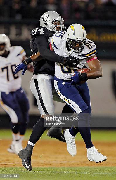 Tight end Antonio Gates of the San Diego Chargers wrestles for extra yards after a catch against linebacker Kevin Burnett of the Oakland Raiders on...