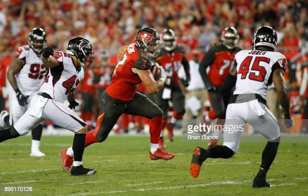 Tight end Antony Auclair of the Tampa Bay Buccaneers runs the ball against outside linebacker Duke Riley of the Atlanta Falcons and middle linebacker...