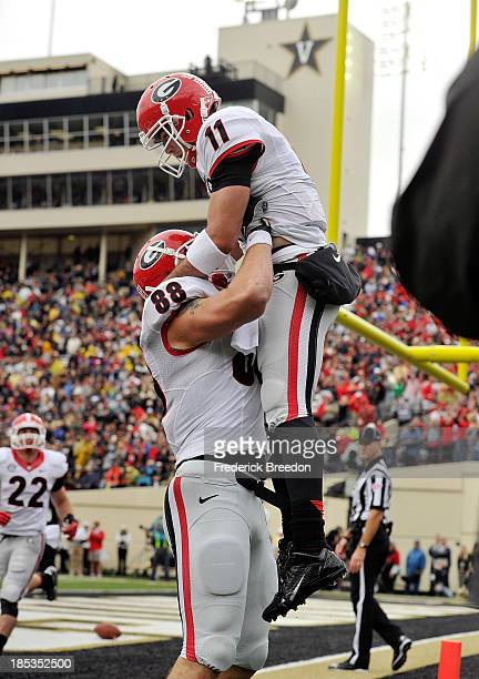 Tight end Arthur Lynch of the Georgia Bulldogs holds up teammate quarterback Aaron Murray after scoring a touchdown against the Vanderbilt Commodores...