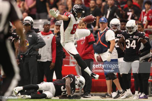 Tight end Austin Hooper of the Atlanta Falcons leaps over safety Deionte Thompson of the Arizona Cardinals after a reception during the first half of...