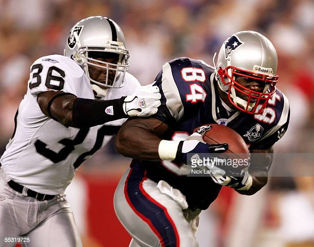 Tight end Ben Watson of the New England Patriots tries to get past strong safety Derrick Gibson of the Oakland Raiders during the 2005 NFL opening...