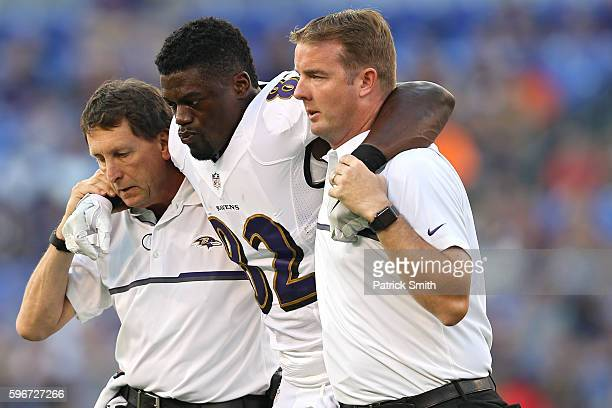 Tight end Benjamin Watson of the Baltimore Ravens is helped off the field by medical staff after being injured against the Detroit Lions during the...