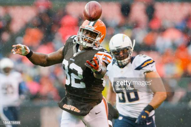 Tight end Benjamin Watson of the Cleveland Browns can't reel in a pass from quarterback Brandon Weeden under pressure from linebacker Antwan Barnes...
