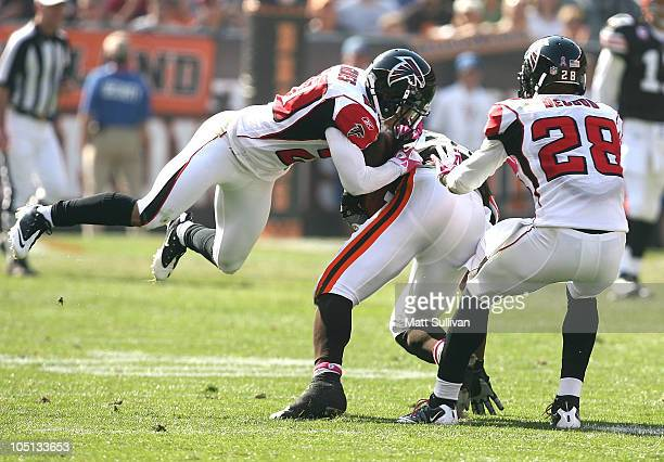 Tight end Benjamin Watson of the Cleveland Browns is tackled by defenders Brent Grimes and Thomas DeCoud of the Atlanta Falcons at Cleveland Browns...