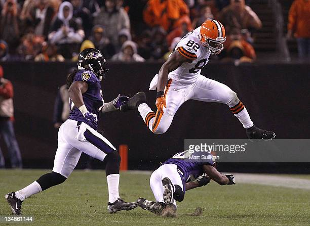 Tight end Benjamin Watson of the Cleveland Browns jumps over safety Ed Reed of the Baltimore Ravens before being hit by linebacker Dannell Ellerbe at...