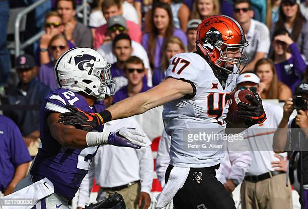 Tight end Blake Jarwin of the Oklahoma State Cowboys rushes up field for a touchdown against free safety Kendall Adams of the Kansas State Wildcats...