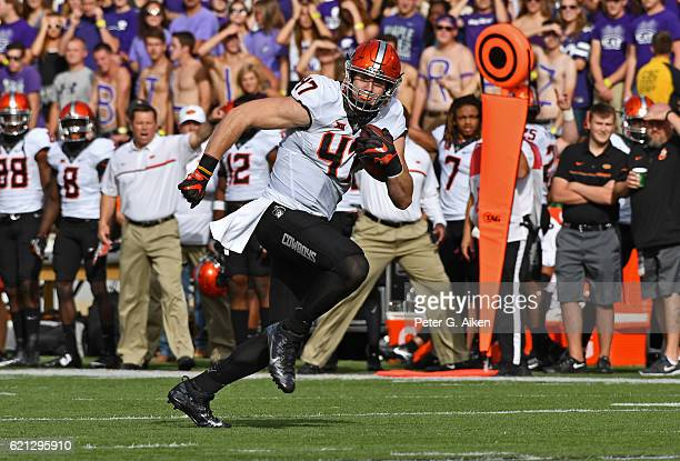 Tight end Blake Jarwin of the Oklahoma State Cowboys rushes up field for a touchdown against the Kansas State Wildcats during the first half on...