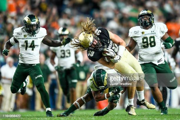 Tight end Brady Russell of the Colorado Buffaloes is hit by safety Jamal Hicks of the Colorado State Rams after a catch and run for a first down in...