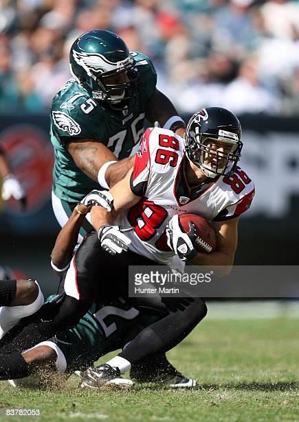 Tight end Brian Finneran of the Atlanta Falcons carries the ball as cornerback Asante Samuel and defensive end Juqua Parker of the Philadelphia...