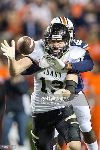 Tight end Buck Cowan of the Idaho Vandals attempts to catch a pass while being wrapped up by defensive back Tim Irvin of the Auburn Tigers on...