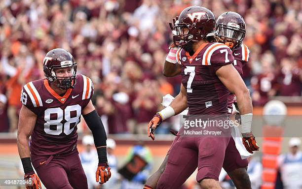 Tight end Bucky Hodges of the Virginia Tech Hokies celebrates his touchdown reception with wide receiver Cam Phillips and tight end Ryan Malleck in...