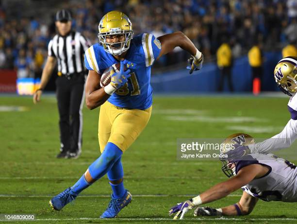Tight end Caleb Wilson of the UCLA Bruins avoids linebacker Ben BurrKirven of the Washington Huskies on a 46 yard pass play in the third quarter of...