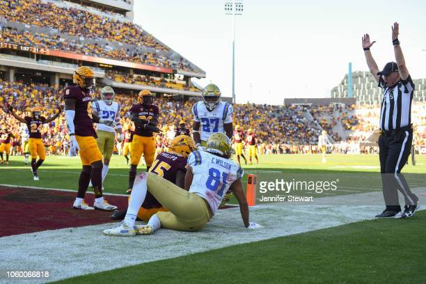 Tight end Caleb Wilson of the UCLA Bruins scores a ten yard touchdown in front of safety Cam Phillips of the Arizona State Sun Devils at Sun Devil...
