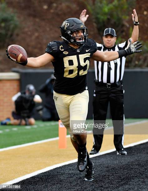Tight end Cam Serigne of the Wake Forest Demon Deacons celebrates after scoring a touchdown against the Presbyterian Blue Hose during their football...