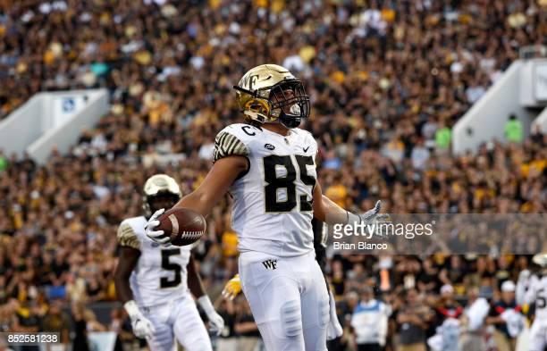 Tight end Cam Serigne of the Wake Forest Demon Deacons celebrates in the end zone after hauling in a pass for a touchdown during the third quarter of...