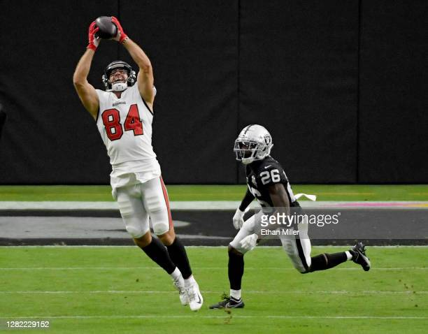 Tight end Cameron Brate of the Tampa Bay Buccaneers catches a pass against cornerback Nevin Lawson of the Las Vegas Raiders during the second half of...