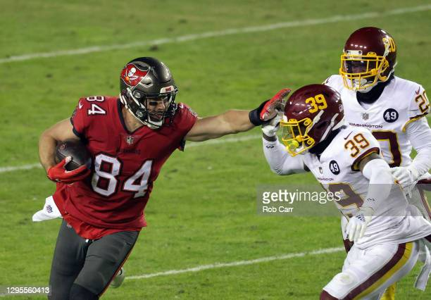Tight end Cameron Brate of the Tampa Bay Buccaneers stiff-arms free safety Jeremy Reaves of the Washington Football Team after making a catch during...