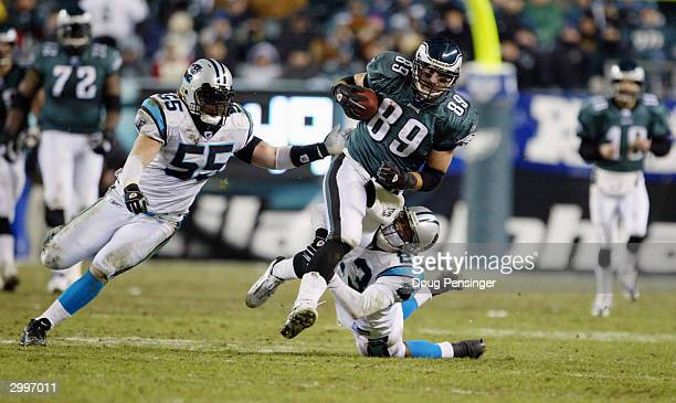 Tight end Chad Lewis of the Philadelphia Eagles evades cornerback Reggie Howard and linebacker Dan Morgan of the Carolina Panthers during the NFC...