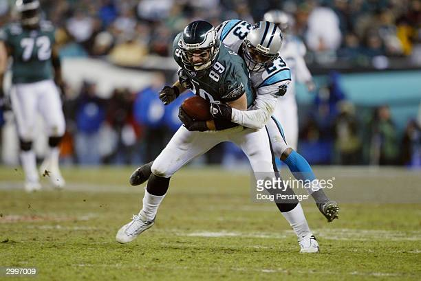 Tight end Chad Lewis of the Philadelphia Eagles is tackled by cornerback Reggie Howard of the Carolina Panthers during the NFC Championship game at...