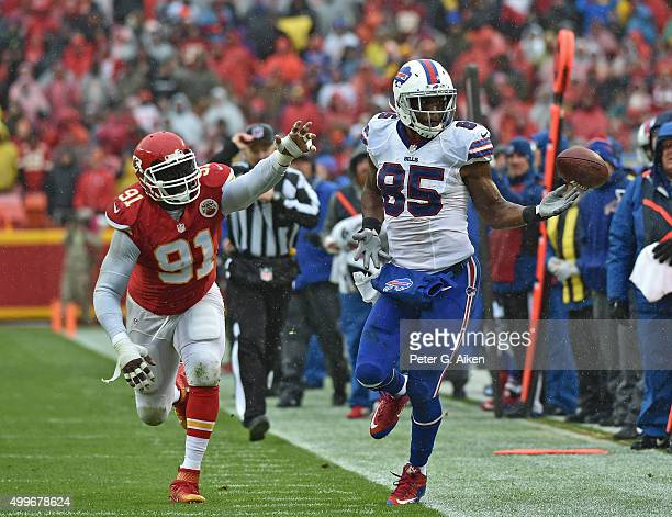 Tight end Charles Clay of the Buffalo Bills reaches out for the ball against linebacker Tamba Hali of the Kansas City Chiefs during the first half on...