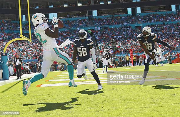 Tight end Charles Clay of the Miami Dolphins catches a first quarter touchdown pass from quarterback Ryan Tannehill with linebacker Donald Butler of...