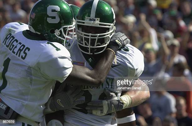 Tight end Chris Baker of Michigan State University Spartans is congratulated by receiver Charles Rogers after catching a touchdown pass during the...