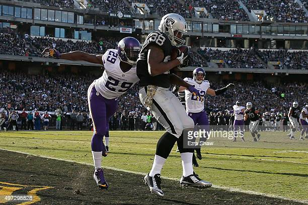 Tight end Clive Walford of the Oakland Raiders scores a touchdown in the second quarter in front of cornerback Xavier Rhodes of the Minnesota Vikings...