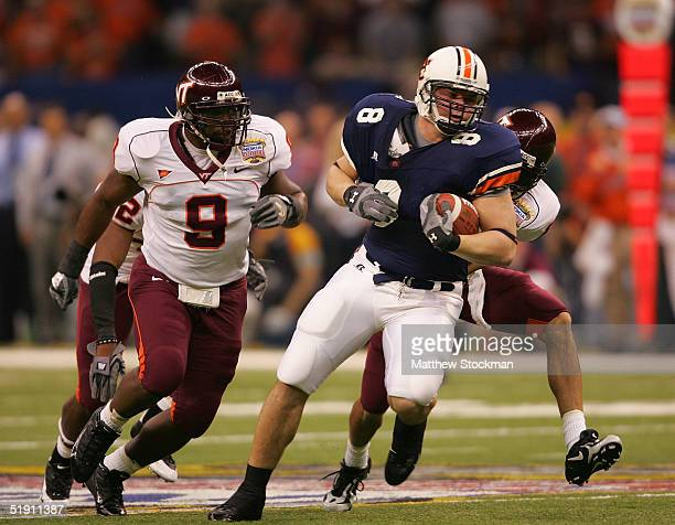 Tight end Cooper Wallace of the Auburn Tigers is pursued by Vince Hall of the Virginia Tech Hokies after a catch during the Nokia Sugar Bowl on...