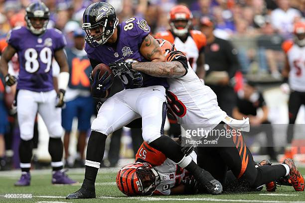 Tight end Crockett Gillmore of the Baltimore Ravens is tackled by middle linebacker Rey Maualuga of the Cincinnati Bengals and outside linebacker...