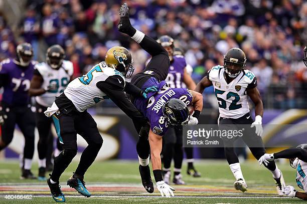 Tight end Crockett Gillmore of the Baltimore Ravens is upended by outside linebacker Geno Hayes of the Jacksonville Jaguars in the third quarter of a...