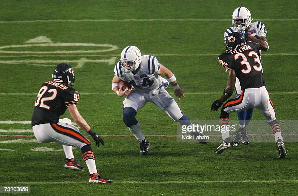 Tight end Dallas Clark of the Indianapolis Colts looks for an opening around the defense of Charles Tillman and Hunter Hillenmeyer of the Chicago...